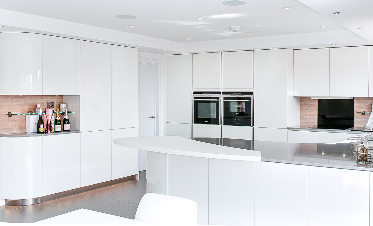 Handleless white curved kitchen with quartz hurstpierpoint for Tall kitchen wall units