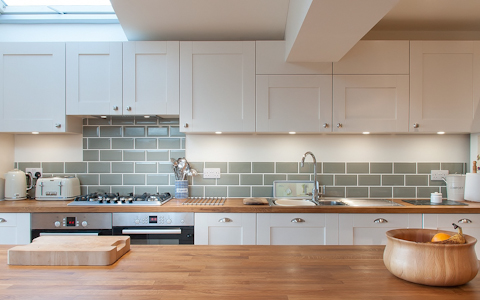 white shaker kitchen with green metro tiles