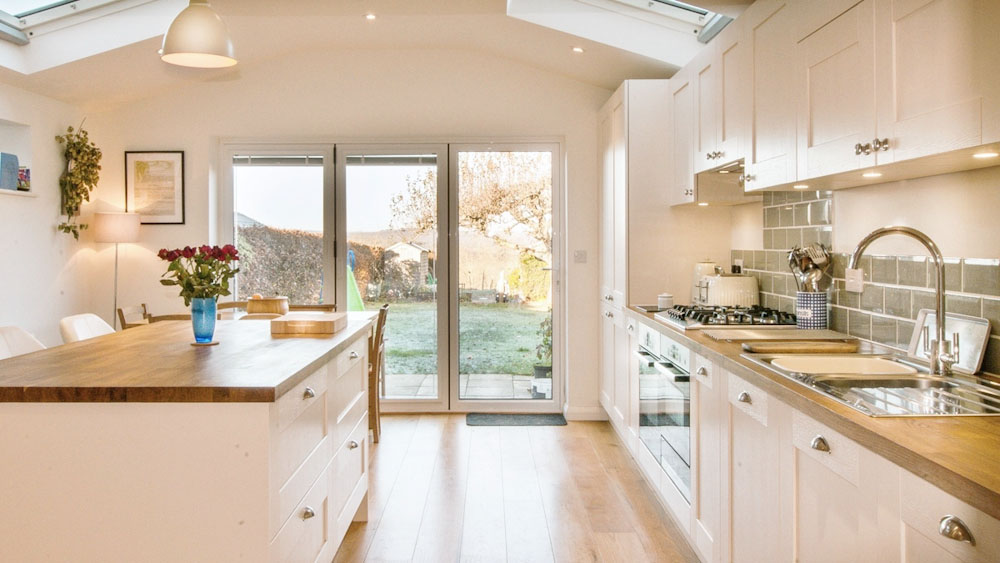 white shaker kitchen with island and bifold doors